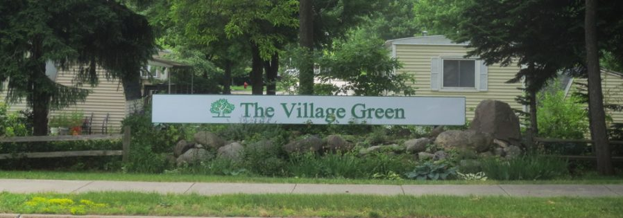 photo of signage on robbins rd. for the village green manufactured home community.